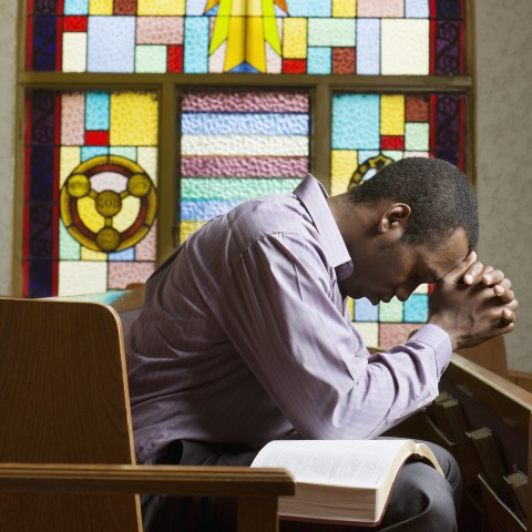 Young Man with Bible on His Lap Praying in Church