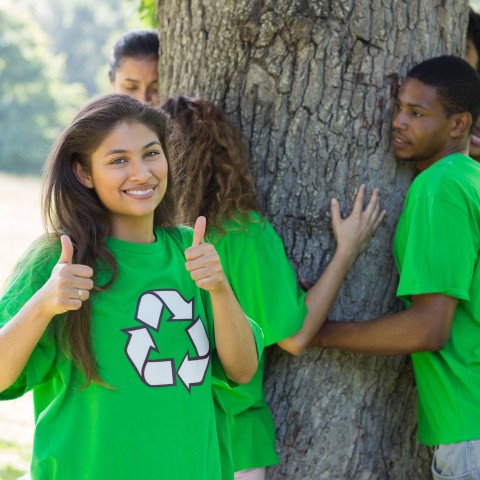 A Girl in a Green Shirt with the Recycle Sign in Front of a tree