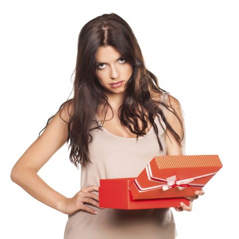 Dark-haired Girl Giving a Very Dirty Look, with One Hand on Her Hip and Holding a Gift Box with Apparent Disgust