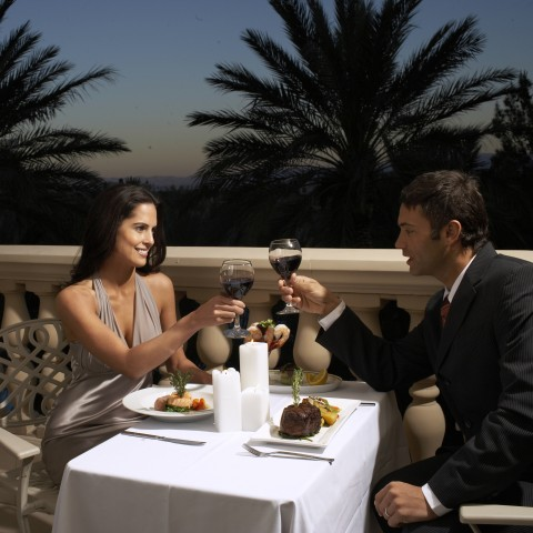 A Romantic Dinner with a Woman and a Man Drinking Wine