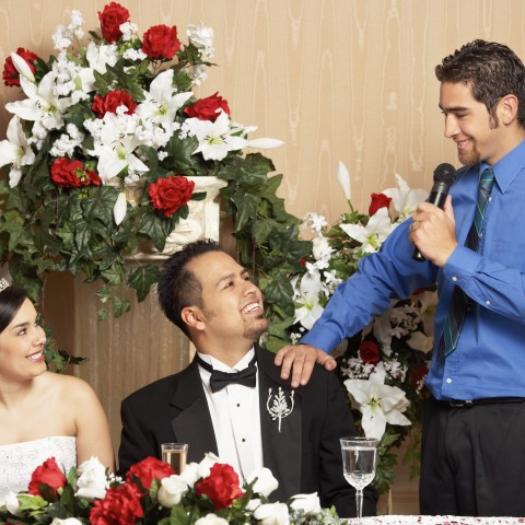 Married Couple During Reception, Sitting at Their Table While a Young Man Gives a Wedding Speech