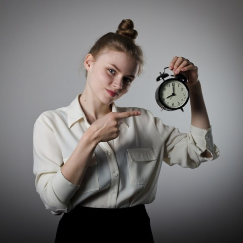 Woman holding an alarm clock in her hand and pointing to it