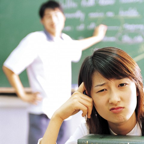 Asian Girl in Classroom Looking Unhappy