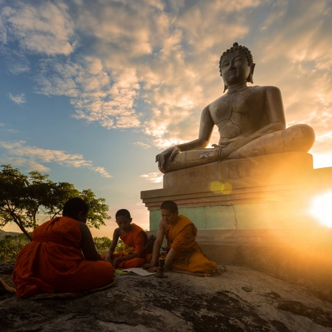 Monks reading on a boulder in front of a Buddha statue