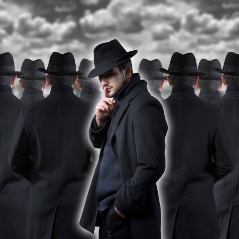 Men in Black Coats and Hats Walking Under Gray Sky