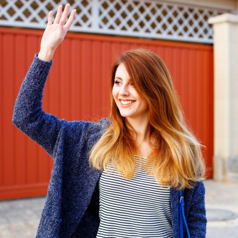 A Girl with a Blue Coat Waving Her Hand