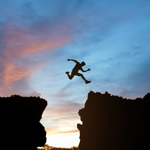 Silhouette of Someone Jumping from One Cliff to Another