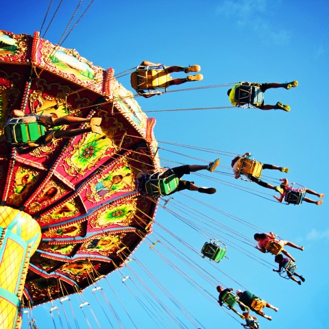 View from below of a carnival swing, with riders directly above the viewer