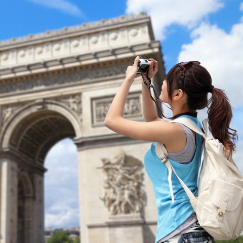 Young Female Tourist with a Backpack Taking a Photo of the Arc de Triomphe