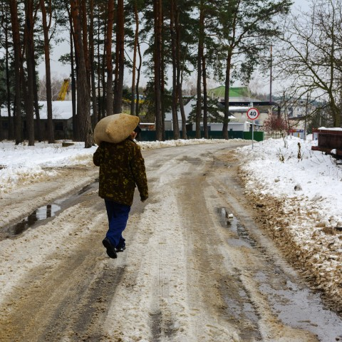 Man Carrying Sack in Snowy Conditions