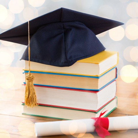 Diploma Hat on Top of a Pile of Books, with a Scroll Next to It