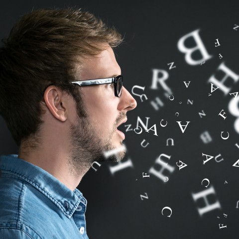 A Man Talking with Letters Coming Out of His Mouth.