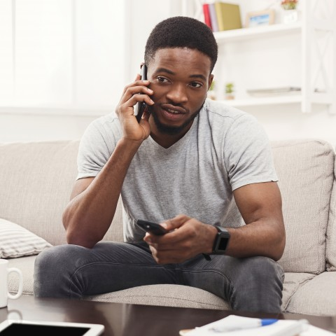Man Flipping through Channels while Talking on the Phone