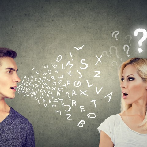 Man and Woman Arguing, with White Alphabet Letters Coming from the Man's Mouth and White Question Marks Above the Woman