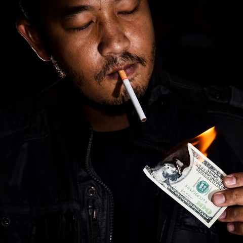Man Lighting Cigarette with Burning Money