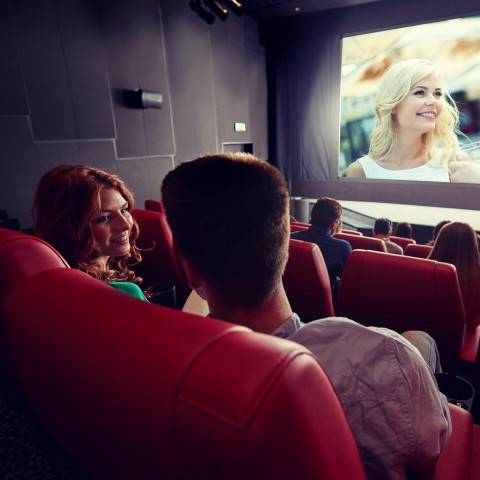Couple Chatting Inside a Cinema with a Movie Screen