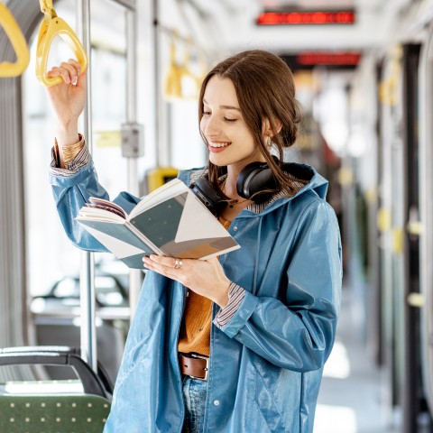 Woman Reading Book on Bus