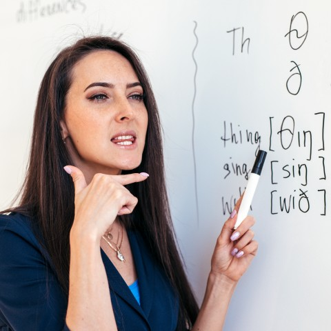 A woman teaching pronunciation in a classroom