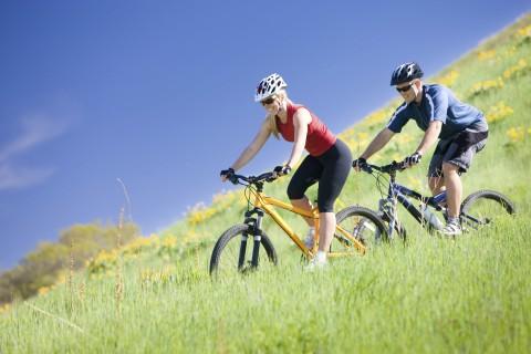 Man and Woman Biking in Field