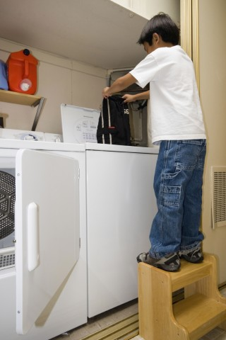 A Kid at Home Standing on a Chair Filling the Washing Machine with Clothes