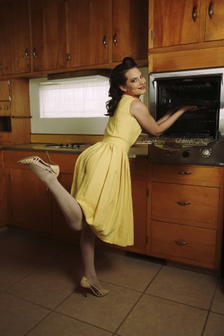 A Woman in a Yellow Dress Reaching into the Oven