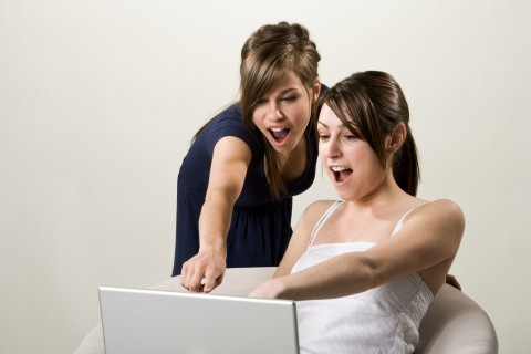Two Young Women Pointing to Something on a Laptop Screen.