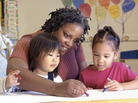 Woman Helping Children with Assignment