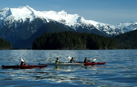 People Kayaking in Lake Near Mountains
