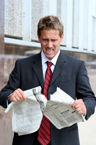 Man Ripping Up Newspaper in Anger