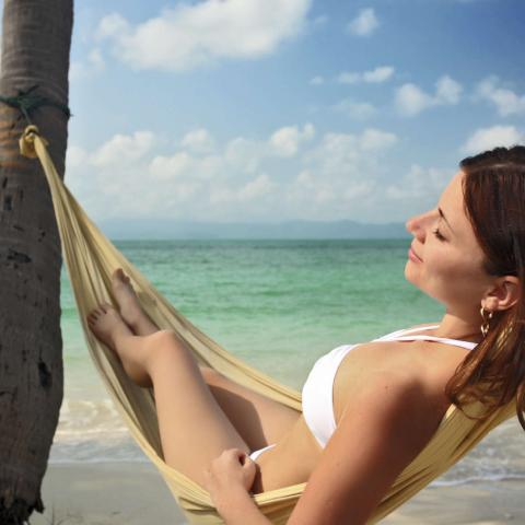 A smiling woman lying in a hammock on the beach