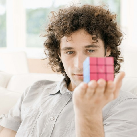 Young man holding a solved rubik's cube