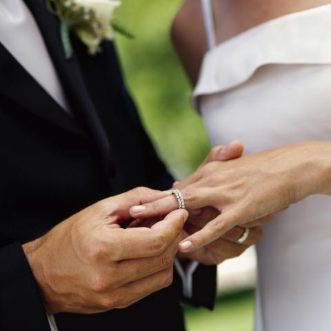 Man Putting Ring on Woman's Finger at Wedding