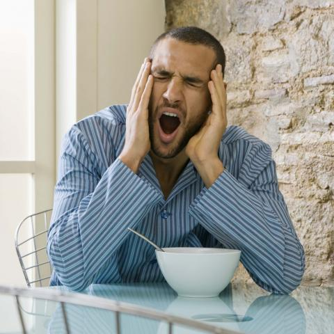 A Man Yawning while Eating Breakfast