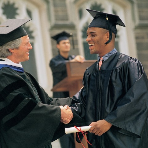 Lecturer or University Dean Congratulating and Handing Over Graduation Certificate to a Young Man on Graduation Day.