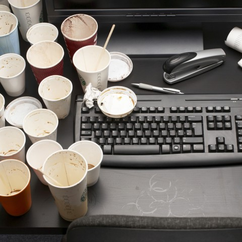 Desk Covered in Empty Coffee Cups